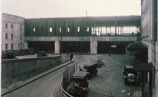 Image shows old cars near a bridge under construction.