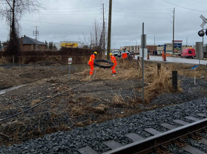 Construction workers run cable near a railway crossing