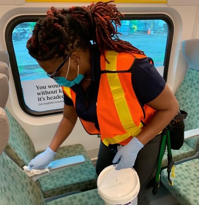 Antonnette Clarke-Thompson wipes off an arm rest as part of her work to disinfect in-service GO trains