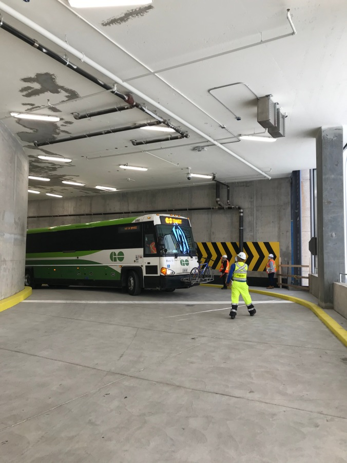 Crews guide a bus down a ramp.