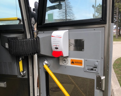 GO bus door with hand sanitizer attached.