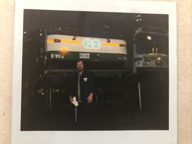 Chris stands in front of a bus.