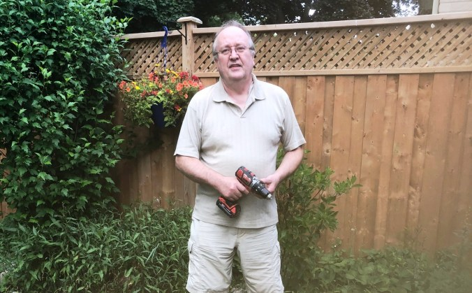 Chris standing in his backyard garden holding a drill