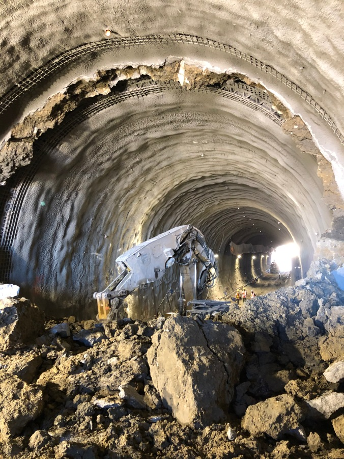 Image shows large rocks in the tunnel, with a digger nearby.