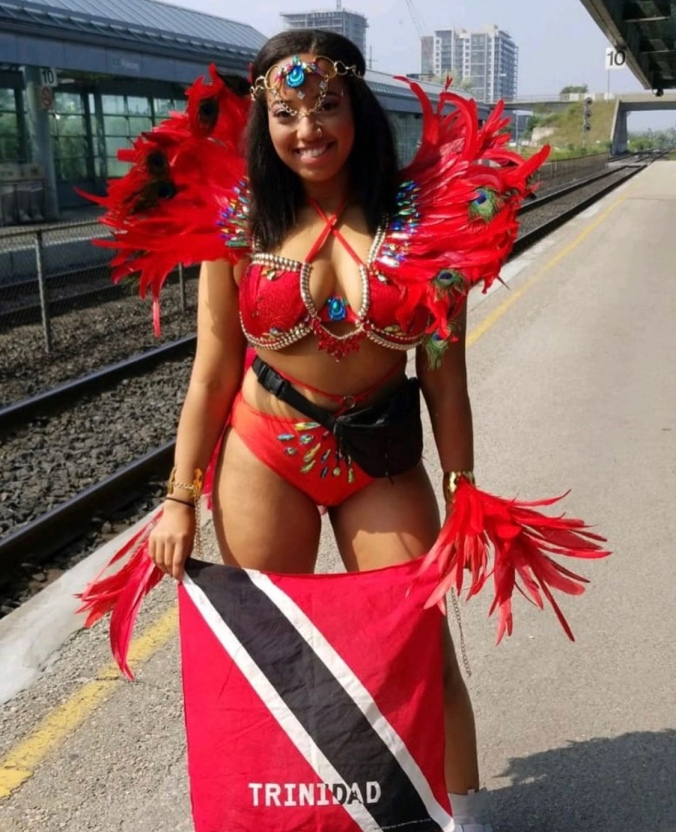 A young woman stands on a train platform while wearing a vibrant costume.