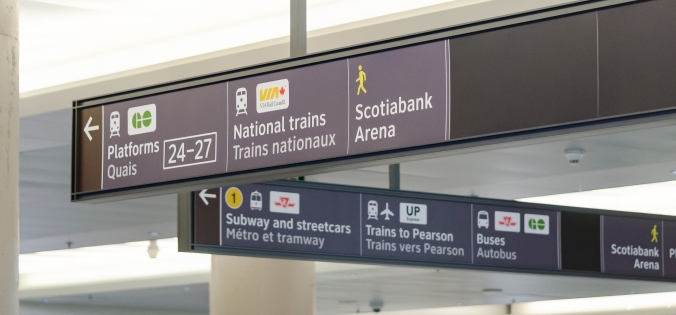 Photo of new wayfinding signs inside Union Station showing directions to GO platforms, VIA and TTC