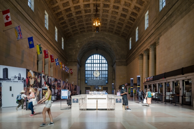 A photo of Inside Union Station's iconic Great Hall with the clock tower and people walking around