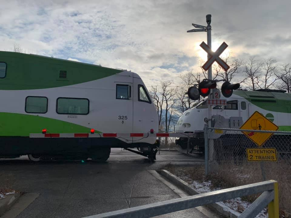 Two GO trains are seen at a crossing.