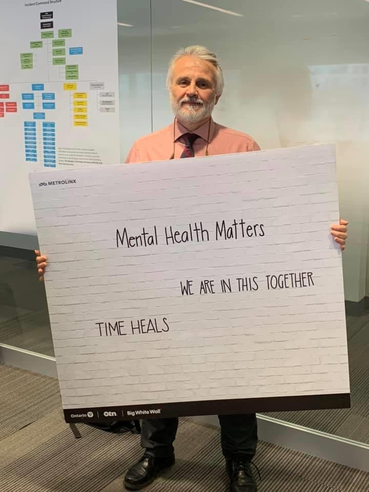 """Vito holds up a sign that reads: """"Mental health matters - We are in this together. Time heals."""""""