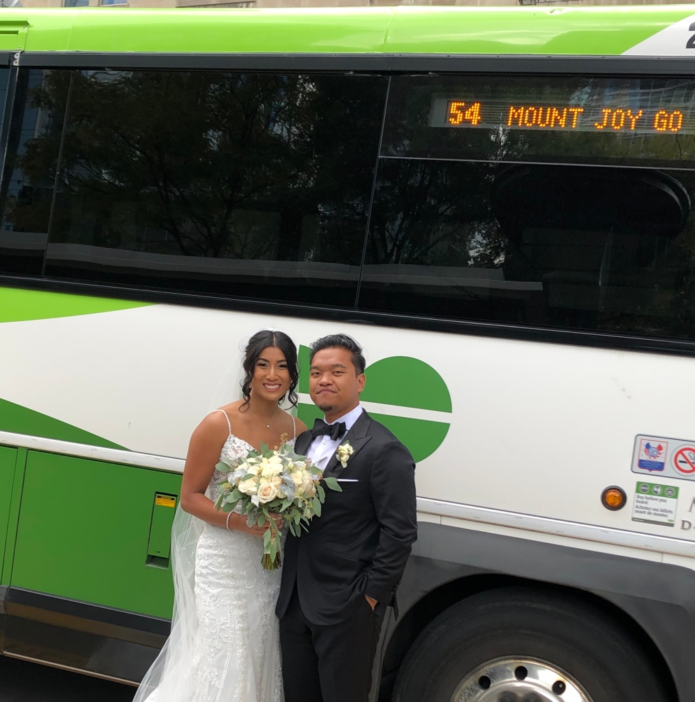 The couple pose beside a GO bus.