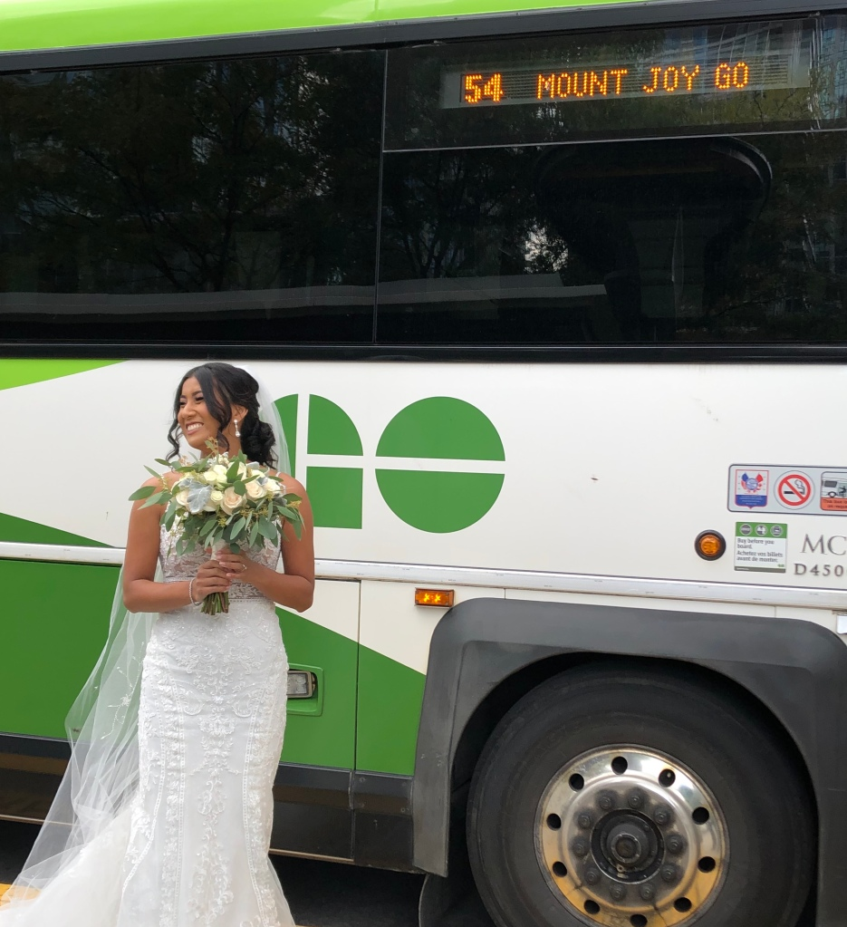 Wearing a bridal dress, Nancy poses beside a GO bus.