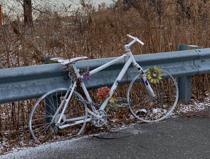 A white painted bike sits next to a guardrail.