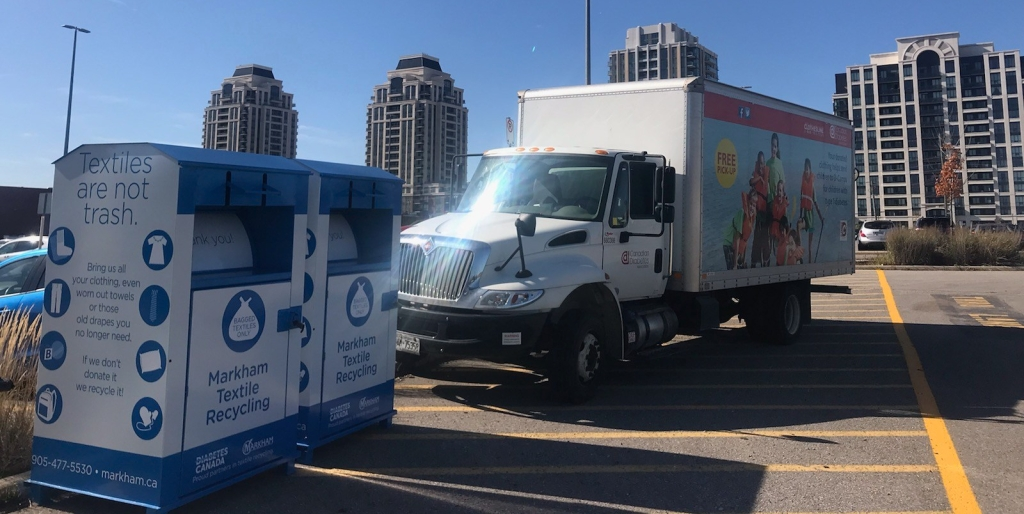 clothing donation bins in the GO Station parking lot with cube van parked next to it