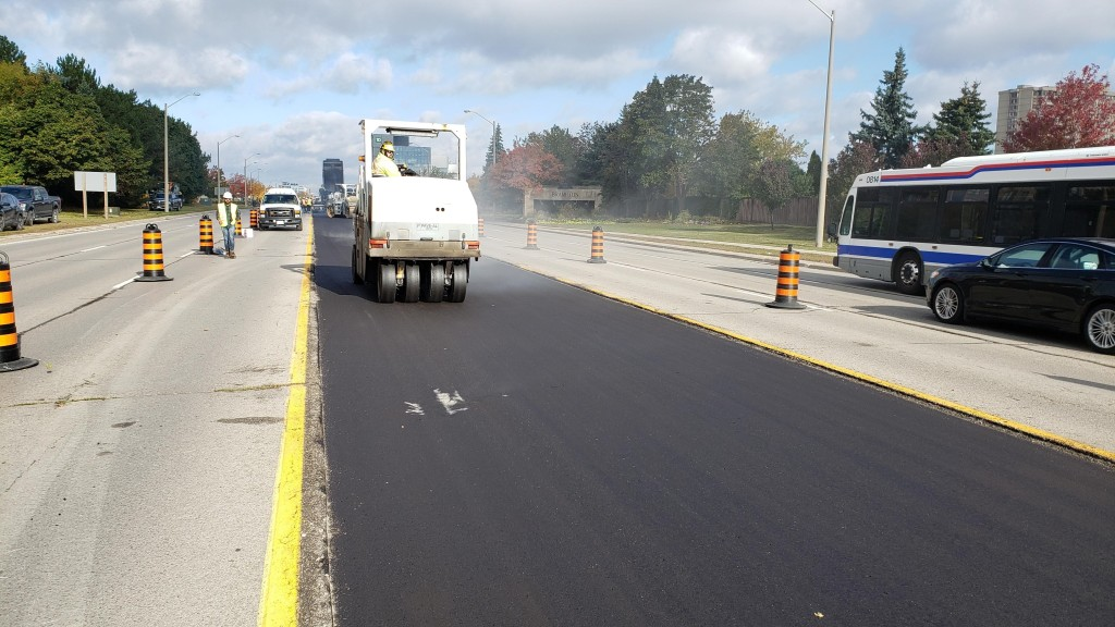 Image shows pavement being put down.