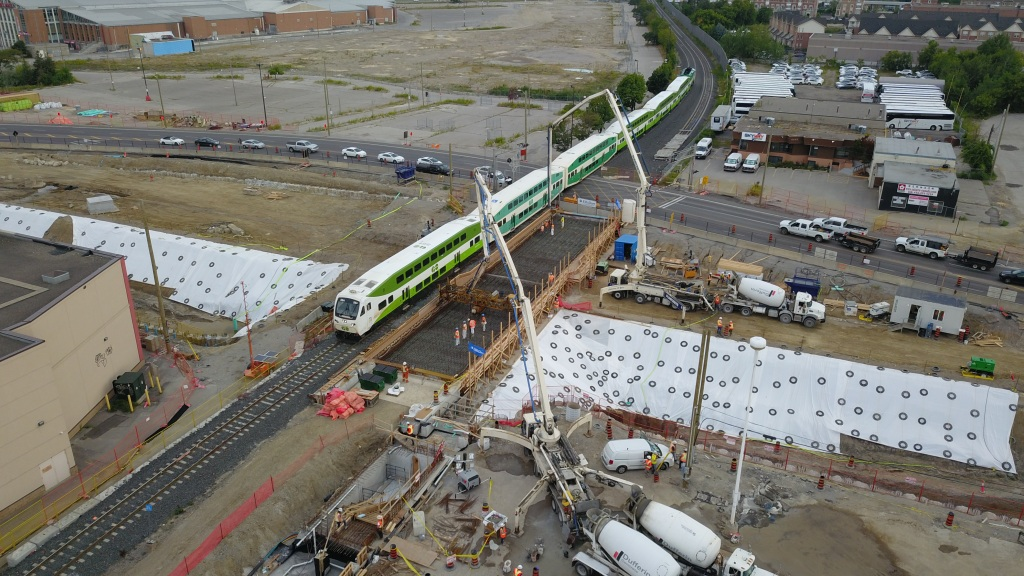 A GO train pass through the Steeles Avenue level crossing while construction goes on