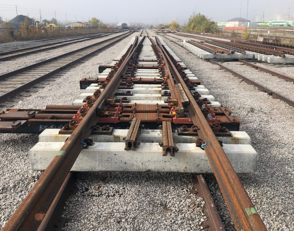 The new switch plant with concrete rail ties sits in the nearby rail yard waiting to be installed.