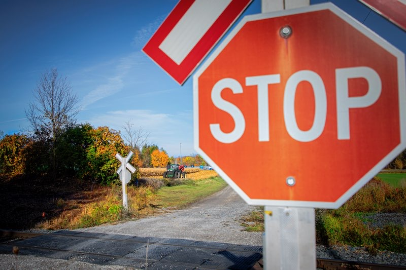 A stop sign sits by a railway track.