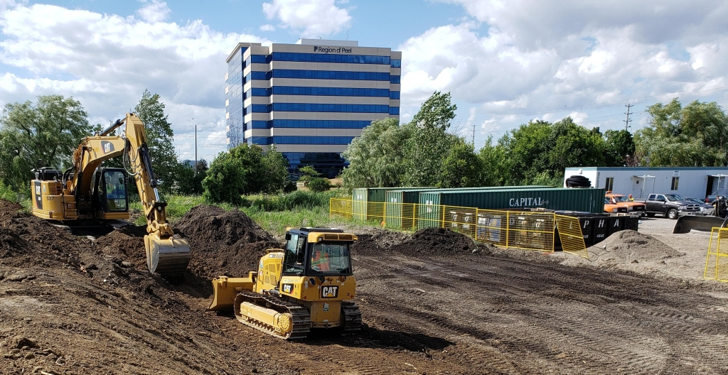 Two tractors work on dirt in a vacant lot.