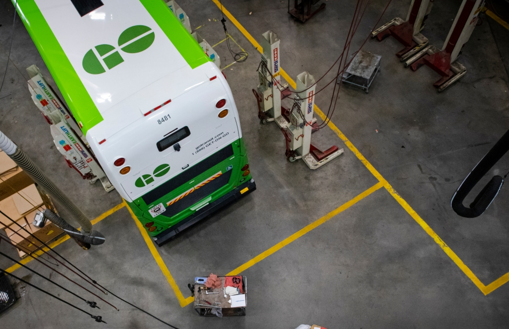 A look down from above, at a worker repairing a bus.