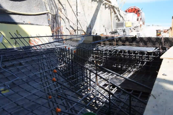 Image shows construction site with metal bars over the pit.