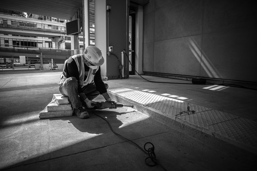 A man uses a grinder on concrete.