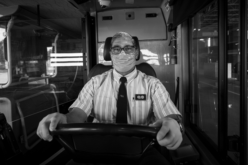 A man sits behind the wheel of a bus.