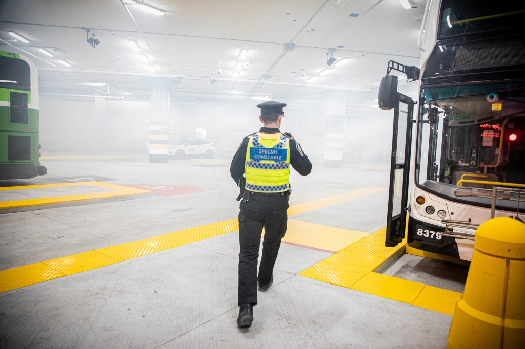 As simulated smoke fills the bus parking area, a Metrolinx Transit Safety officer runs past a vehicle.