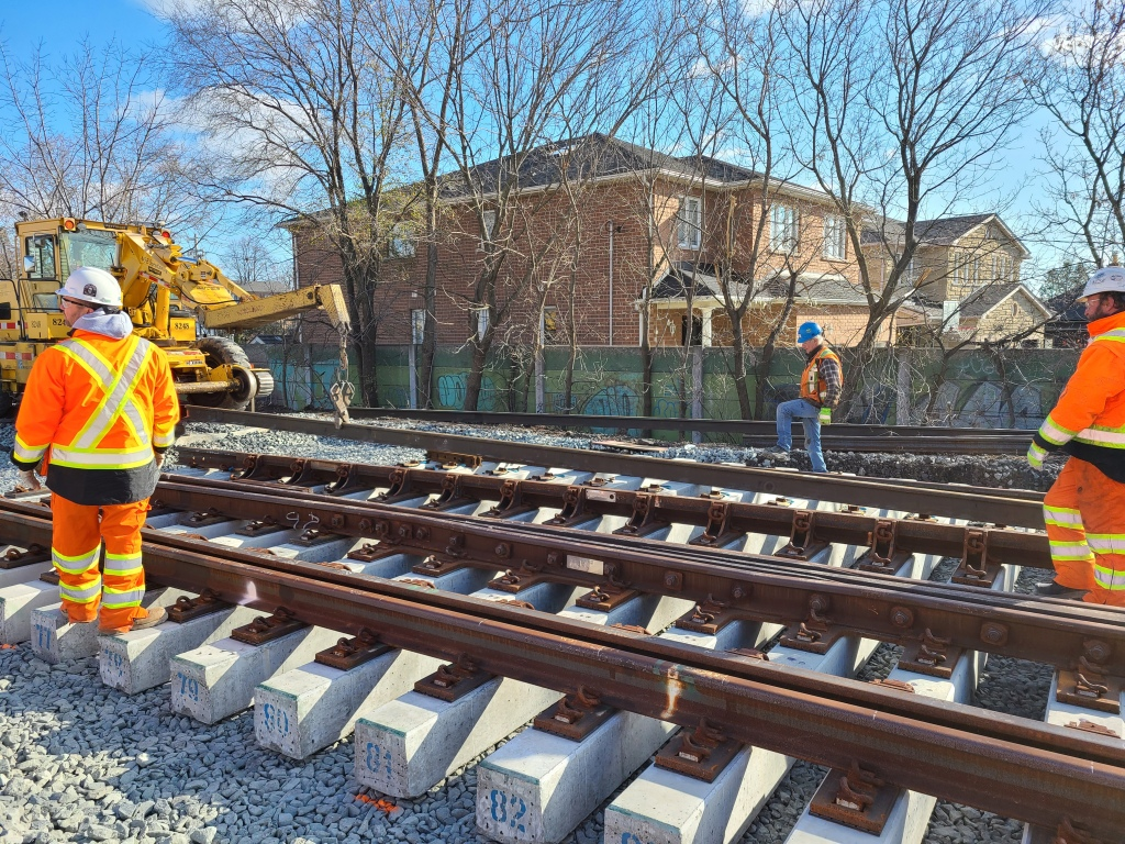 Workers stand next to new sections of rail with concrete rail ties as machinery works in the background