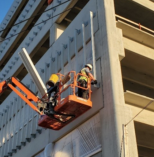workers putting these fins in place, bolting them in one-by-one to brackets affixed to the building.