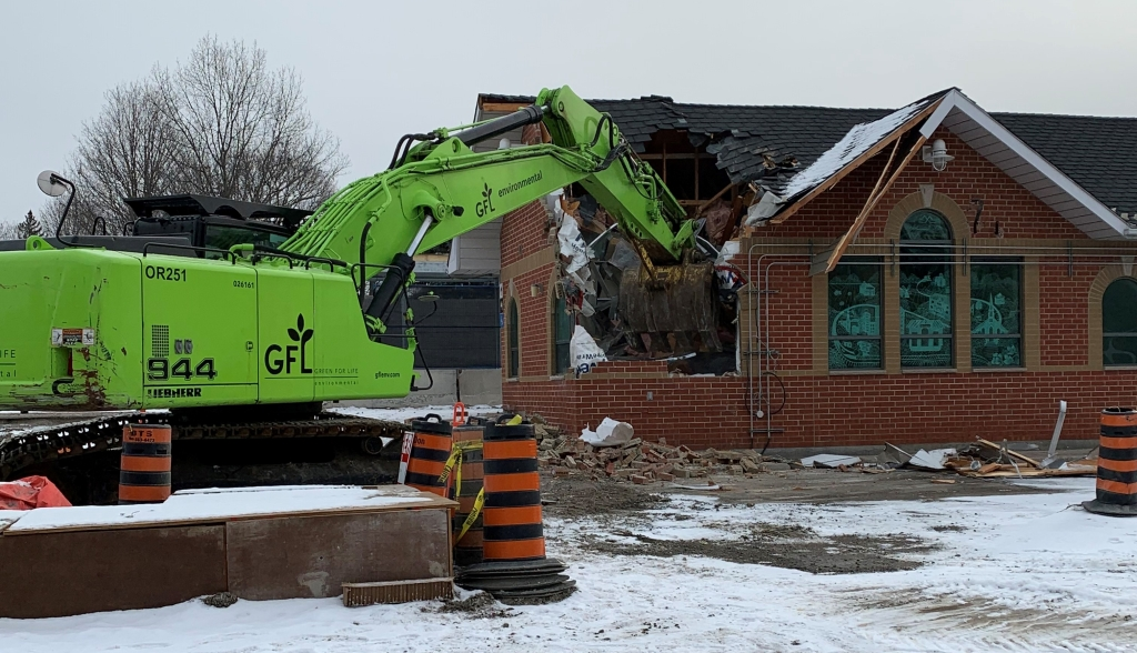 Image shows a tractor digging into the building.