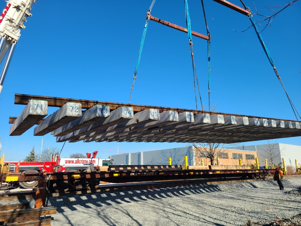 A large piece of track with concrete rail ties is lowered into place by a crane